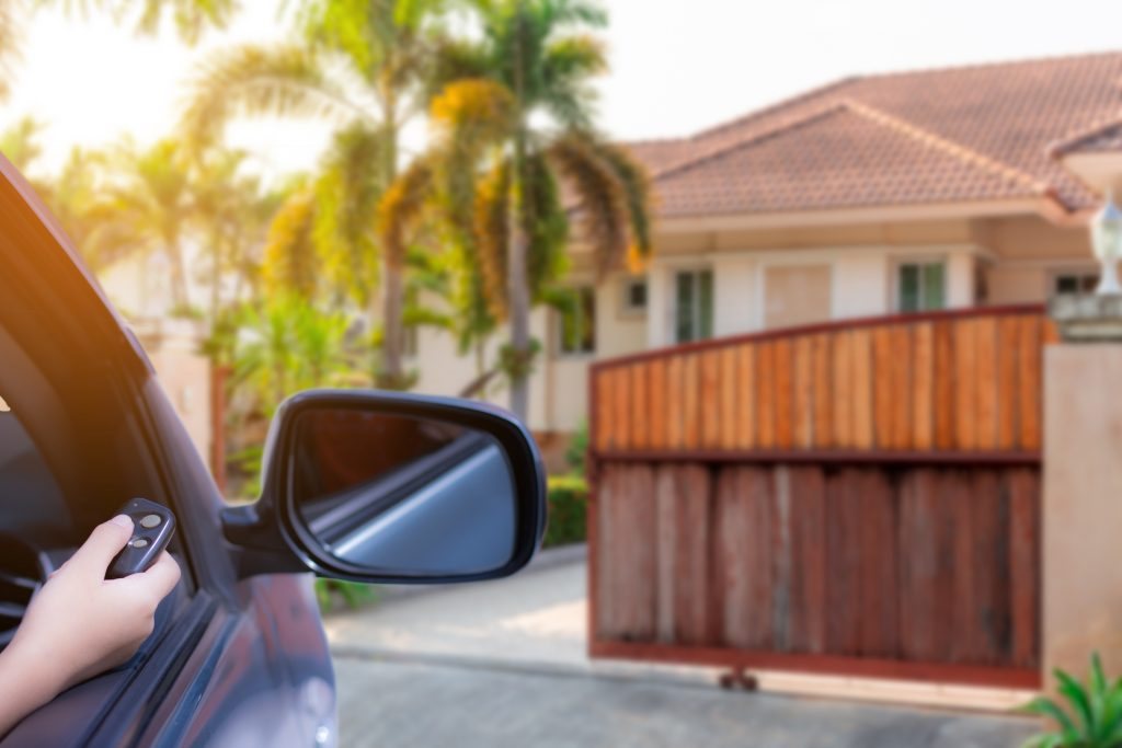 A car outside a home about to enter the gates