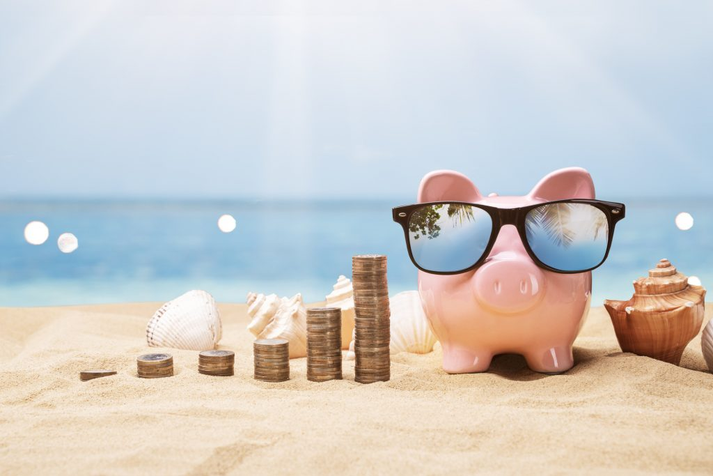 Piggy bank taking a payment holiday on the beach