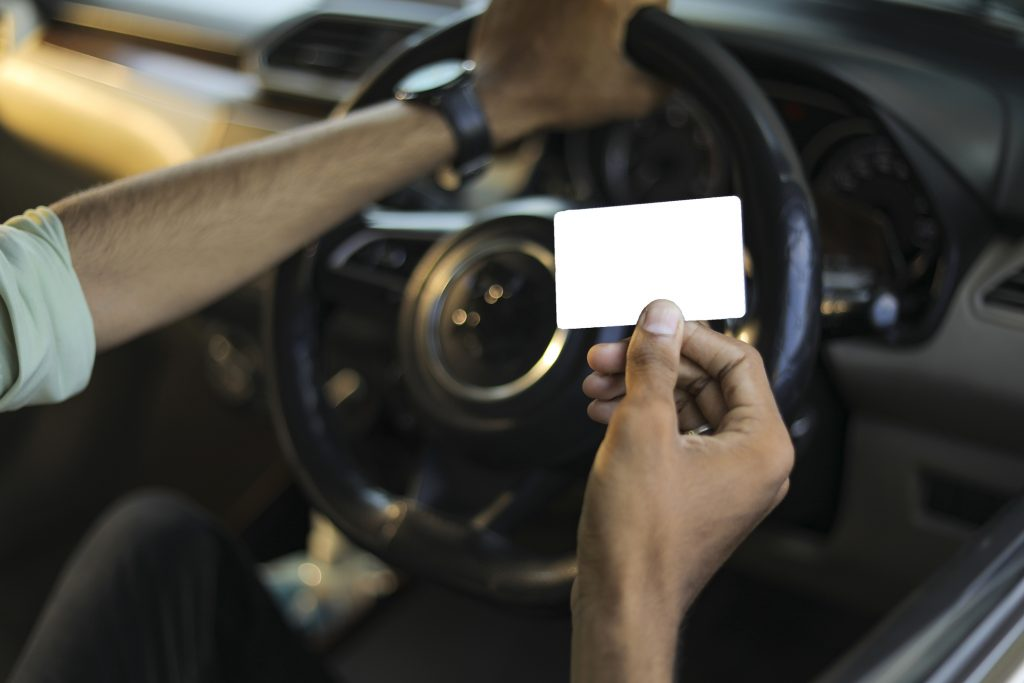 Business man using a credit card while driving