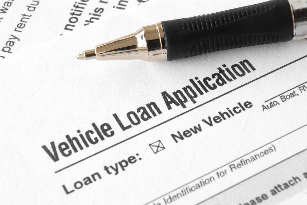 A car finance application with a pen on top