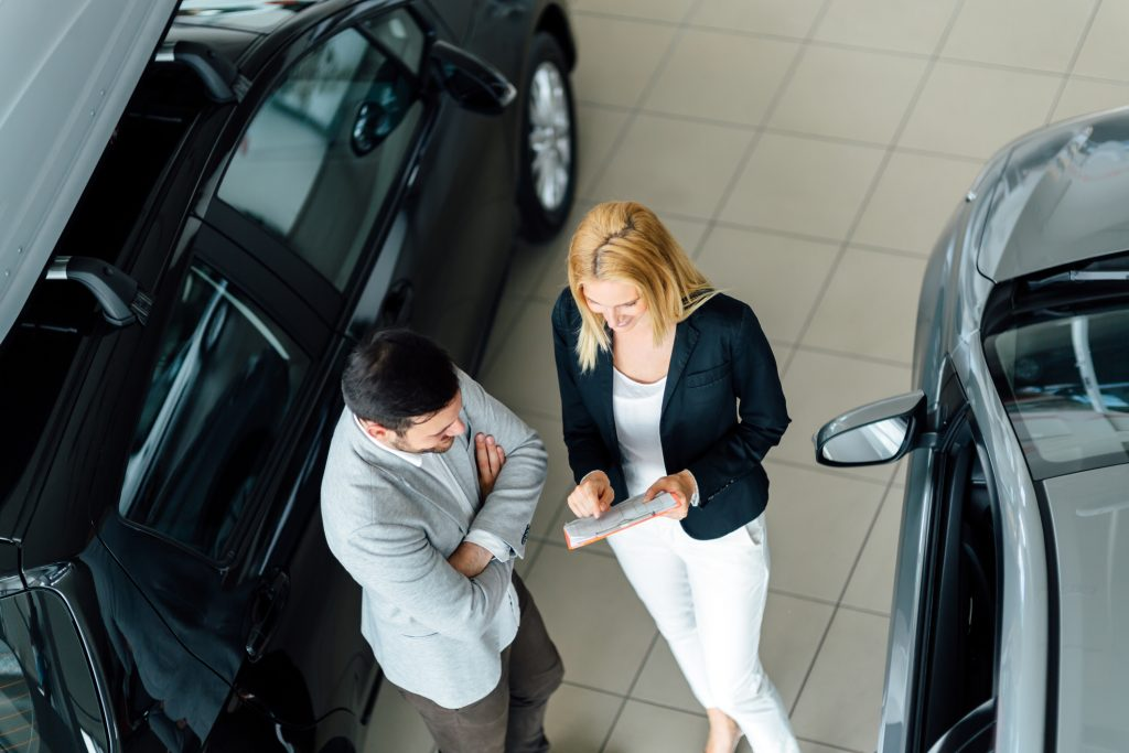 Man looking to get the best deal on a new car in a showroom