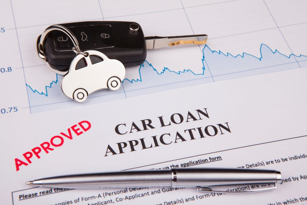 Car loan form with car key and a pen