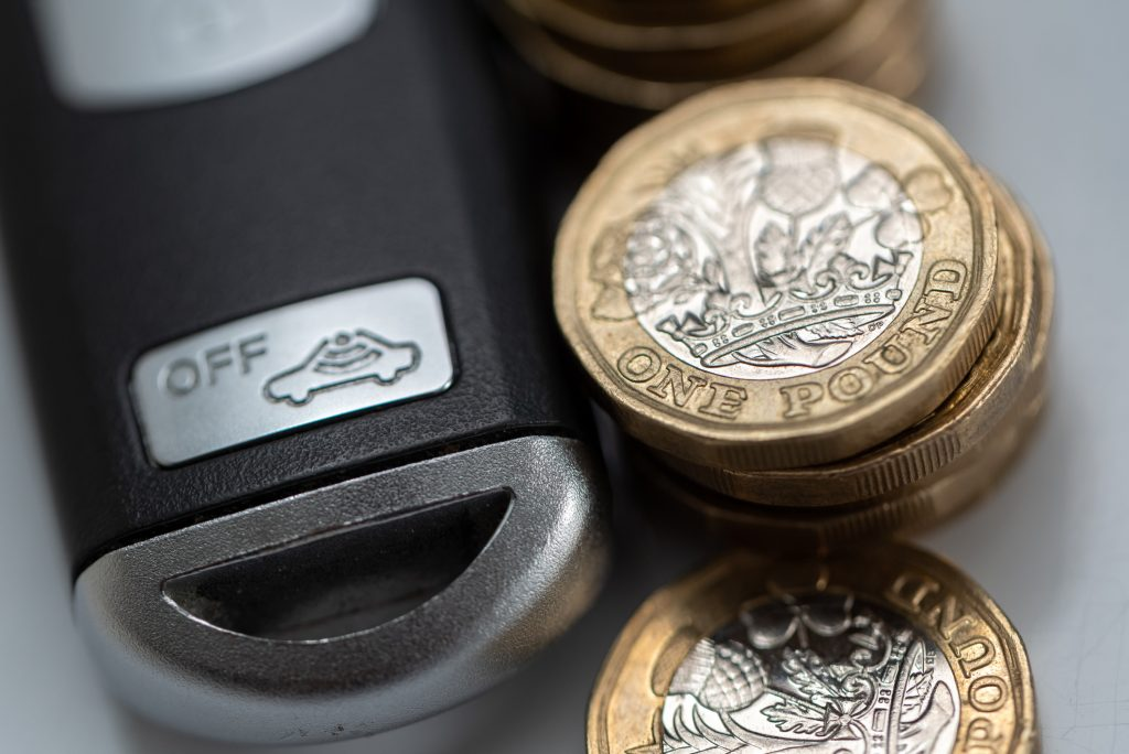 Modern car's remote key by stack of UK pound coins