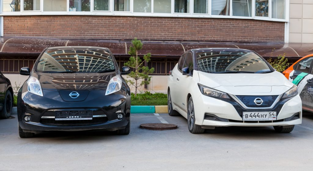 Two electric cars of Japanese production Nissan Leaf on the asphalt in the city near a multi-storey building. Environmentally friendly transport.
