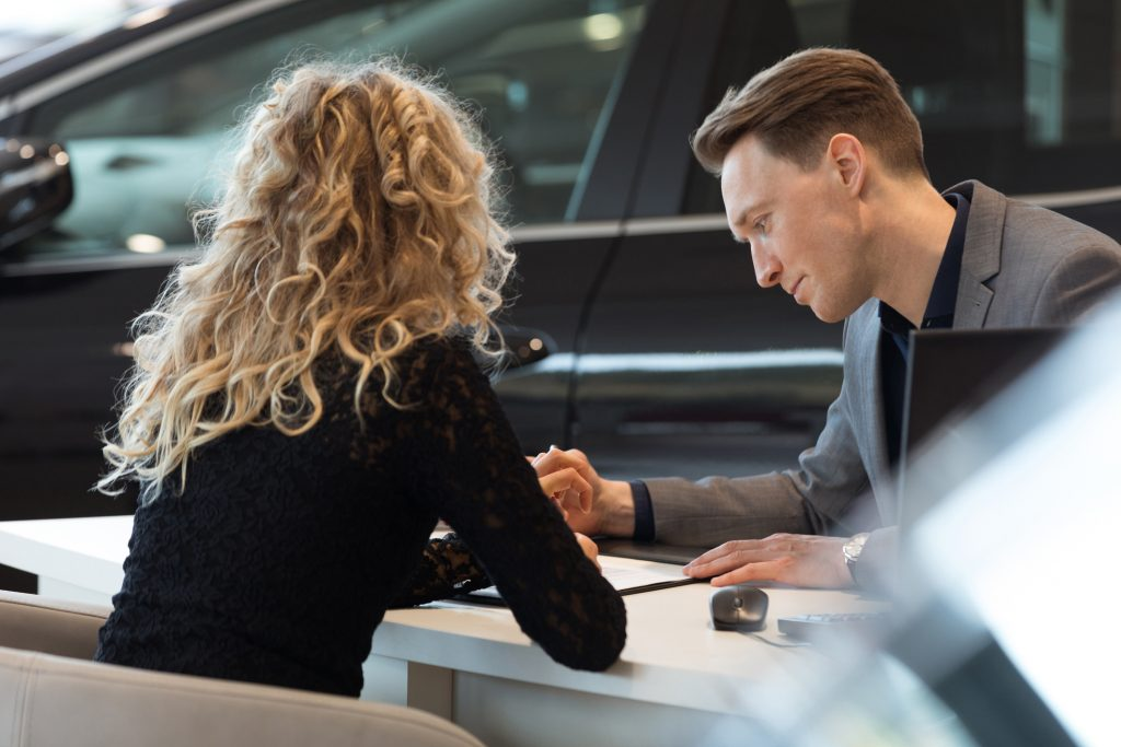 Car salesperson talking with customer in showroom