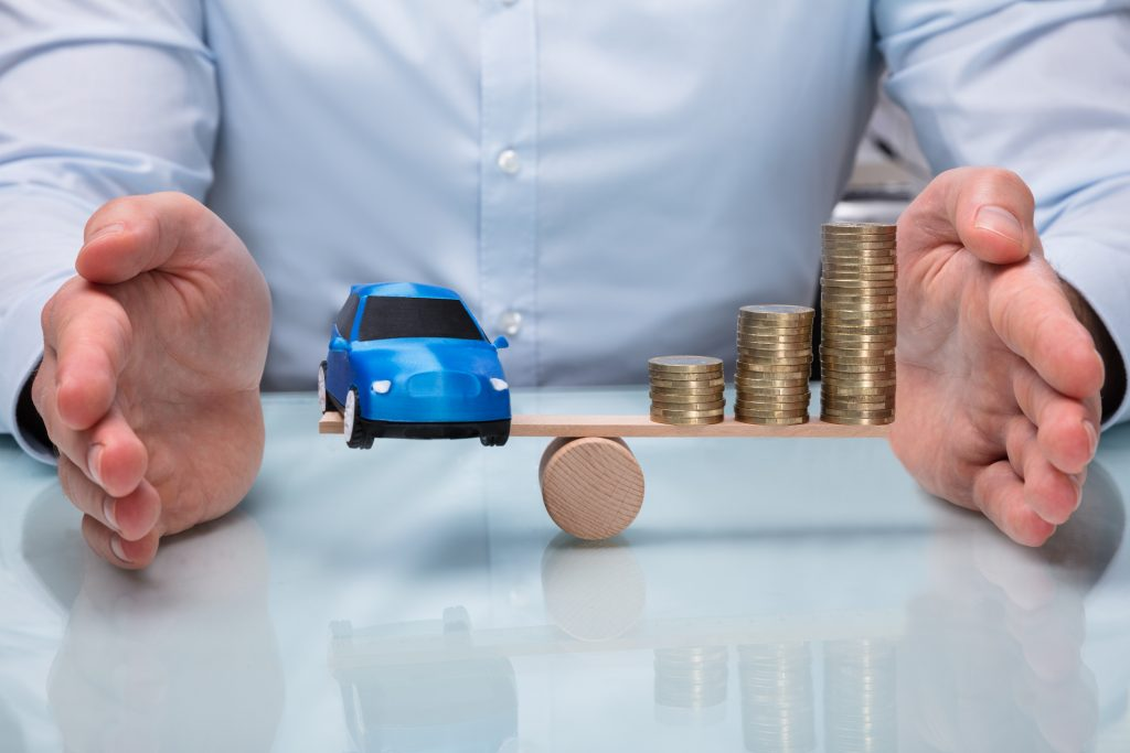 Businessperson Protecting Balance Between Car And Stacked Coins