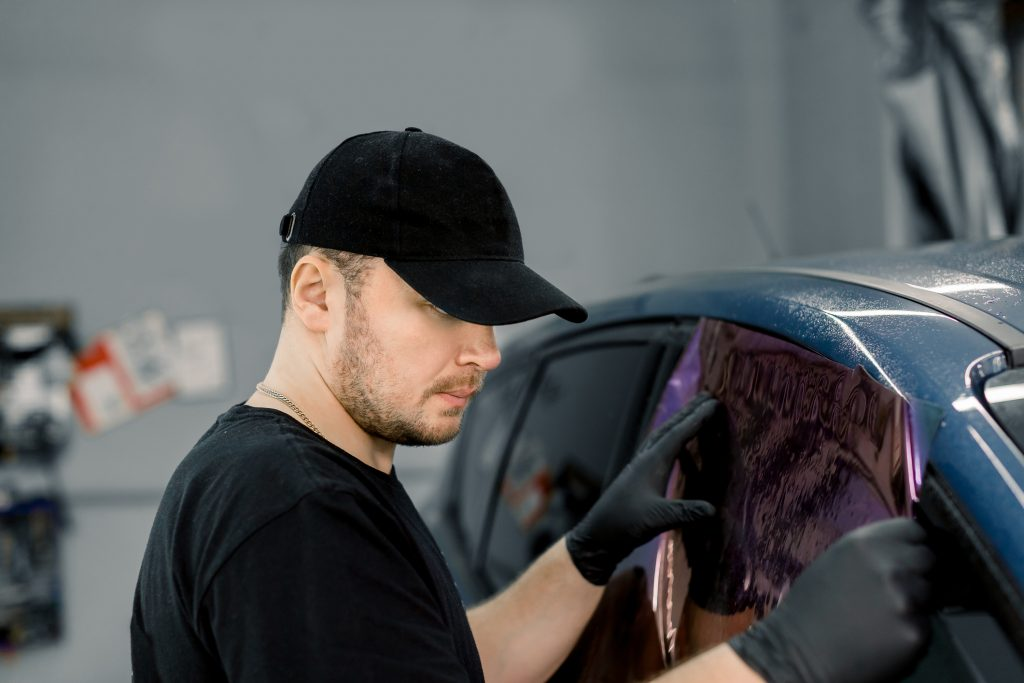 Professional car service worker wearing black cap and t-shirt, tinting a car window with tinted foil or film in auto workshop. Tinting of car windows