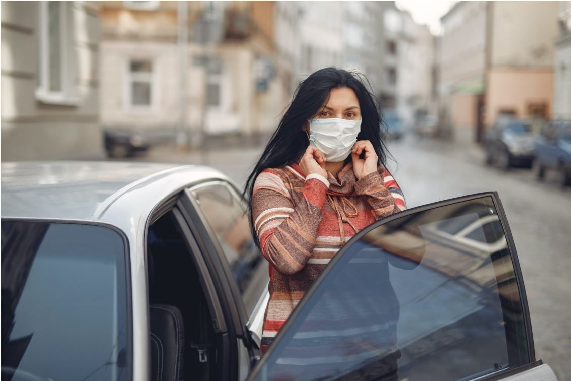 young-woman-wearing-medical-mask-standing-near-automobile-on-3983427