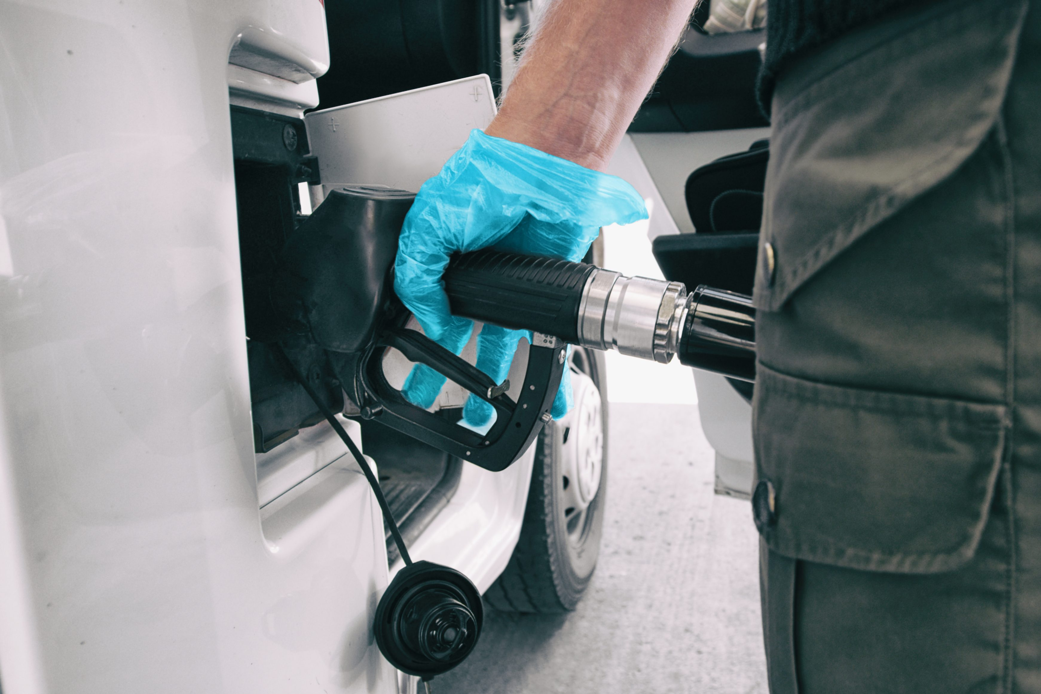 filling car up with glove on