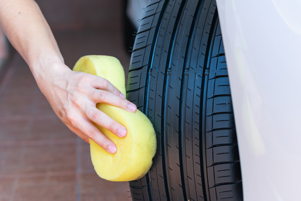 Person cleaning car tyre with sponge