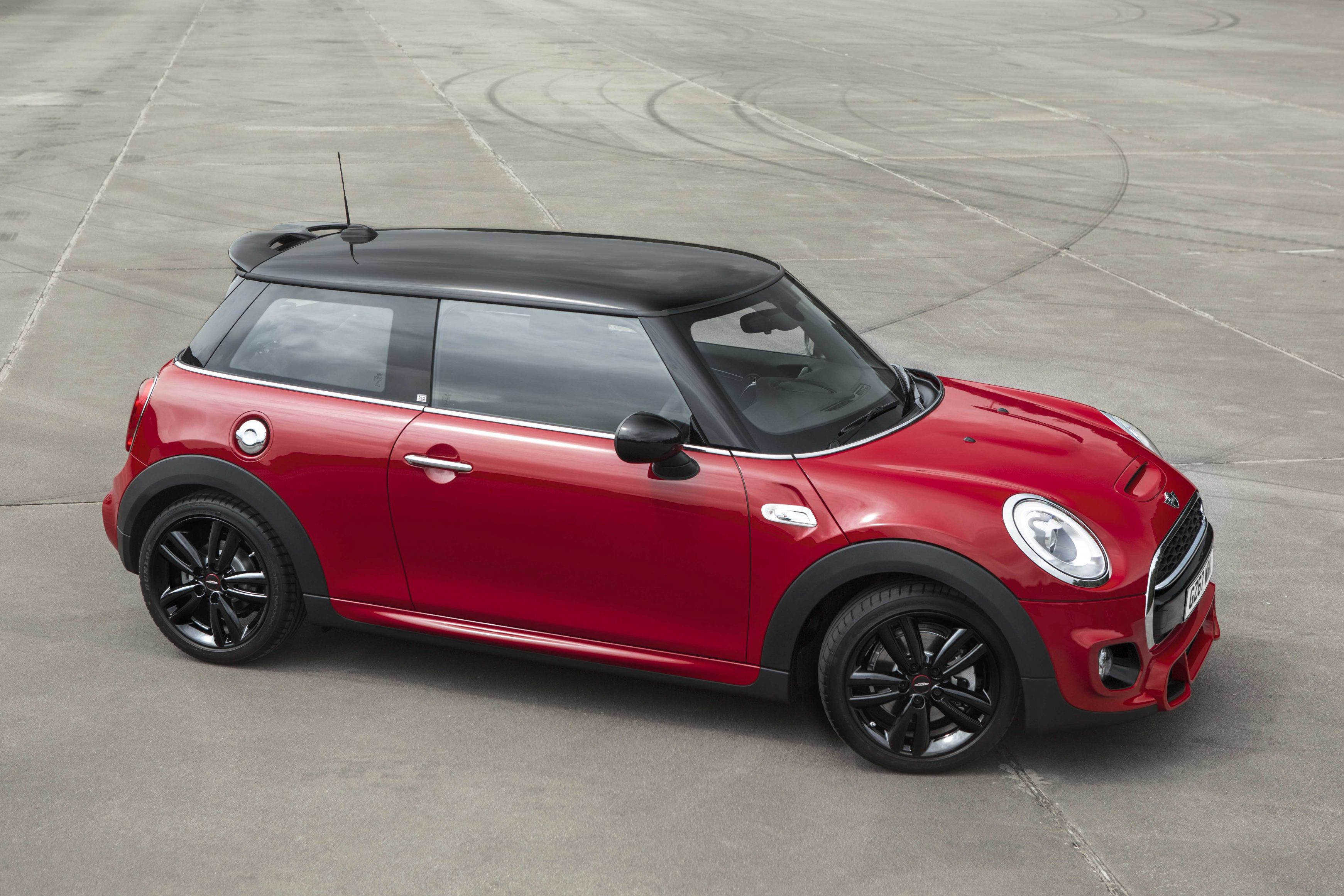 Mini Cooper S in red and black on a plot of land