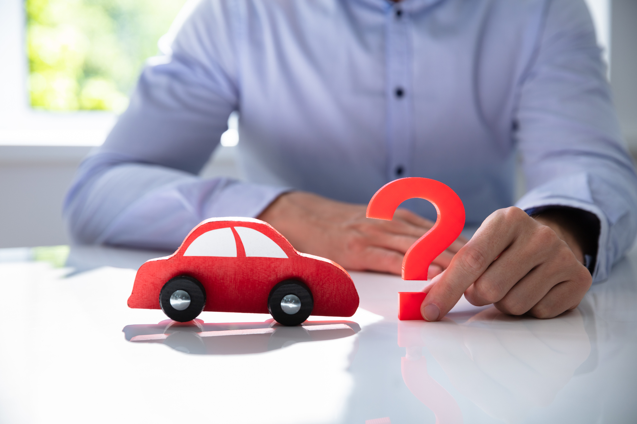 Man holding a wooden car and a question mark