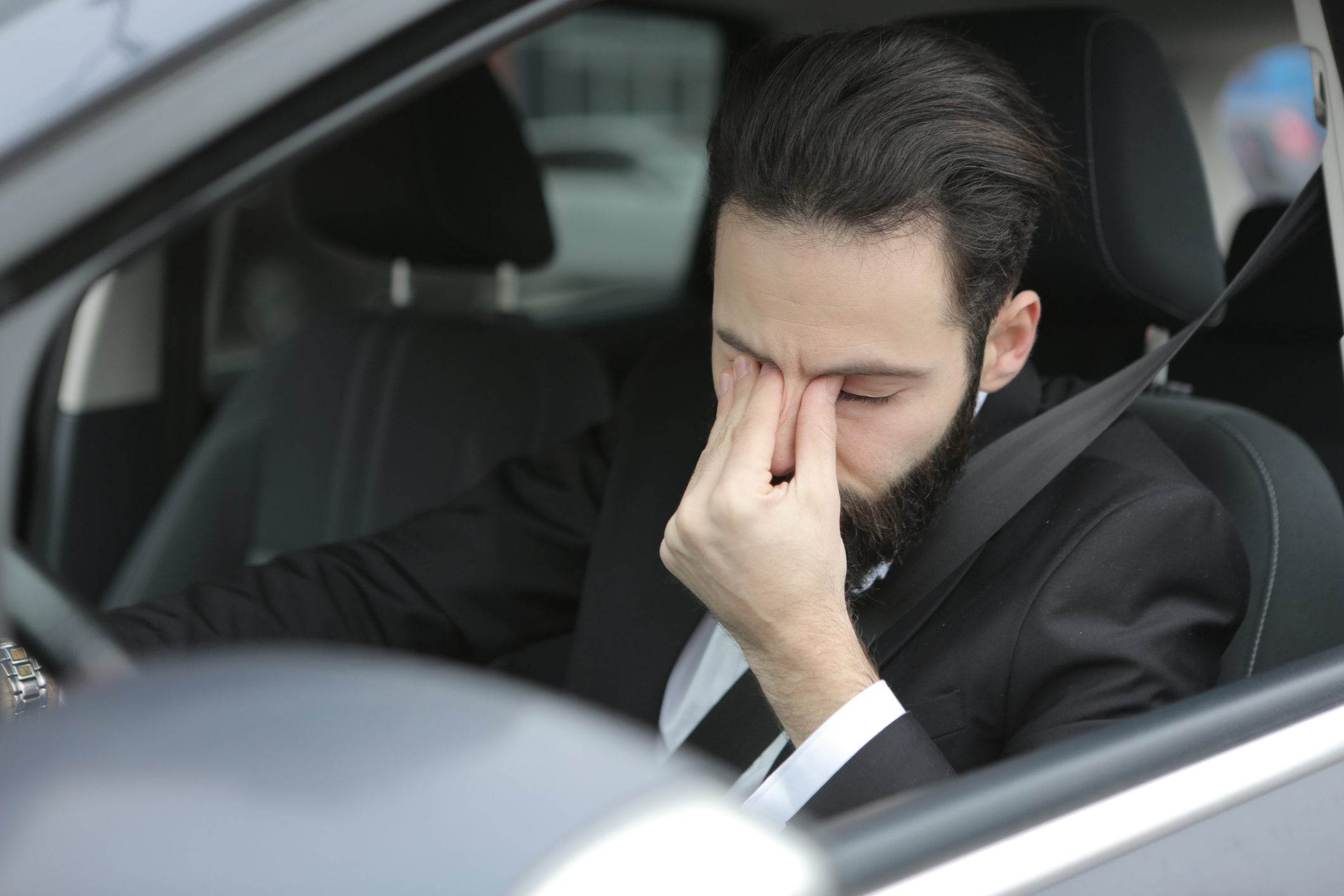 Young man frustrated sat in a car