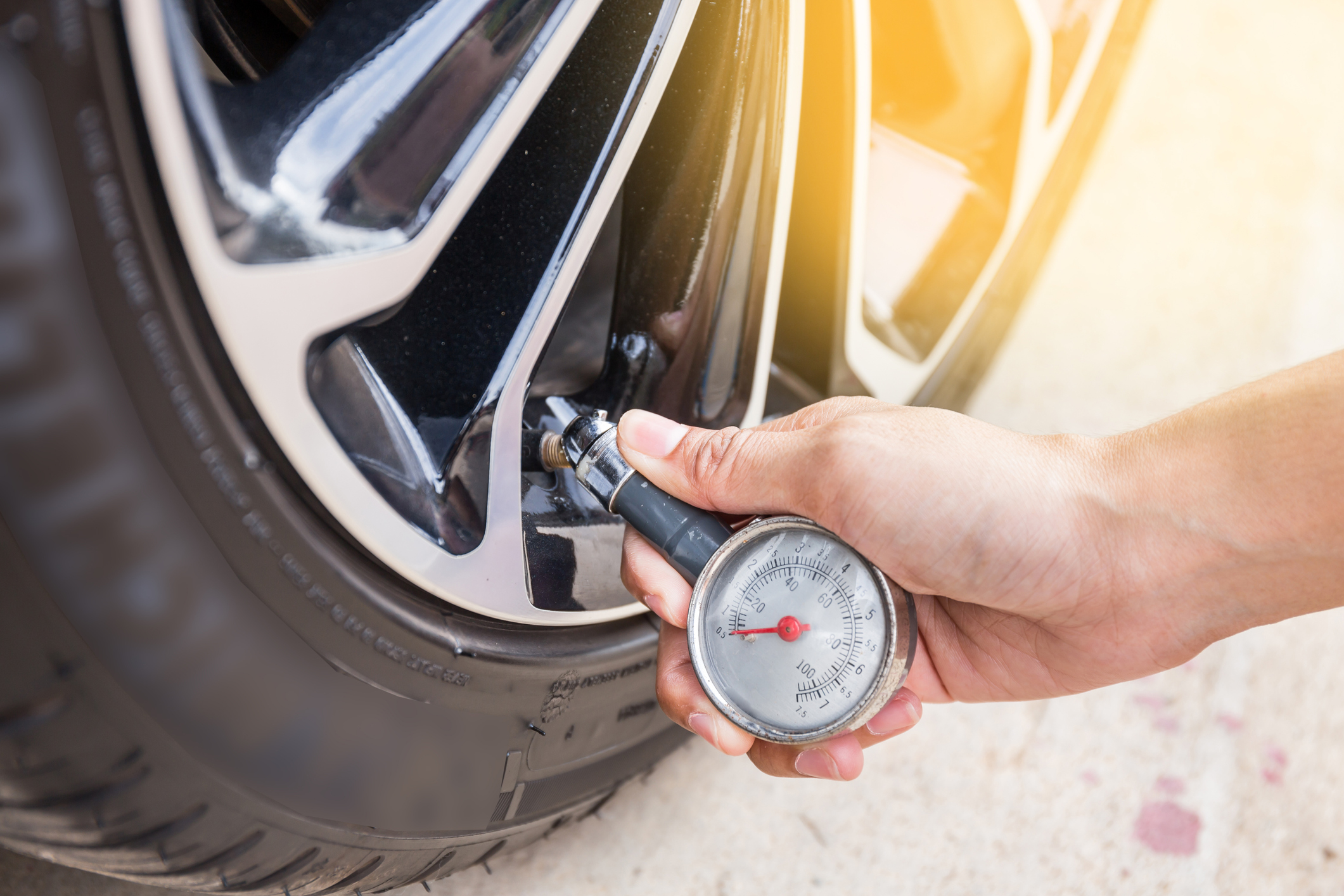 Close-Up Of Hand holding pressure gauge for car tyre pressure