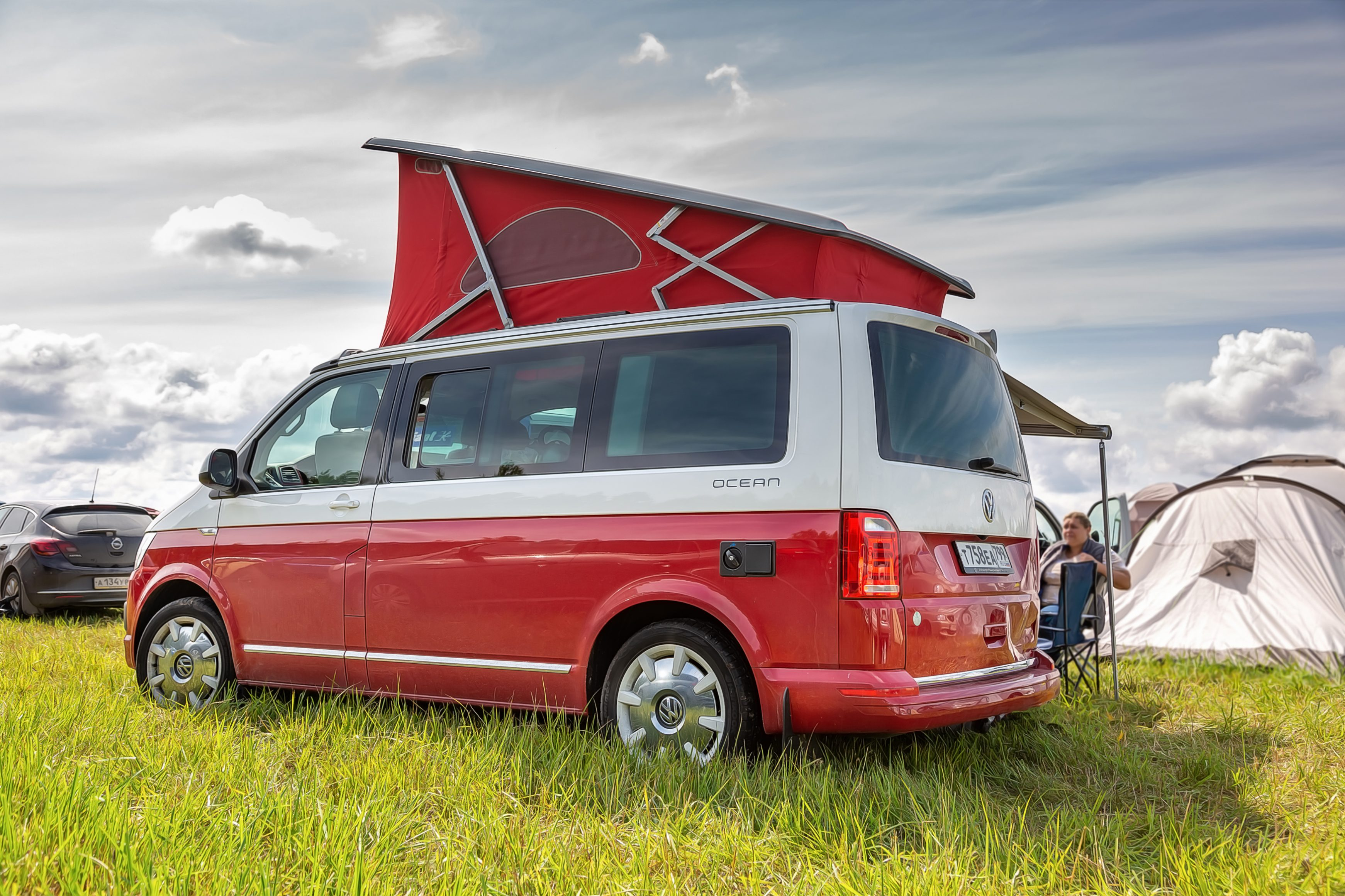 Red and white colored modern Volkswagen Multivan California Ocean (Transporter T6). Parked on the camping field. Back side left view