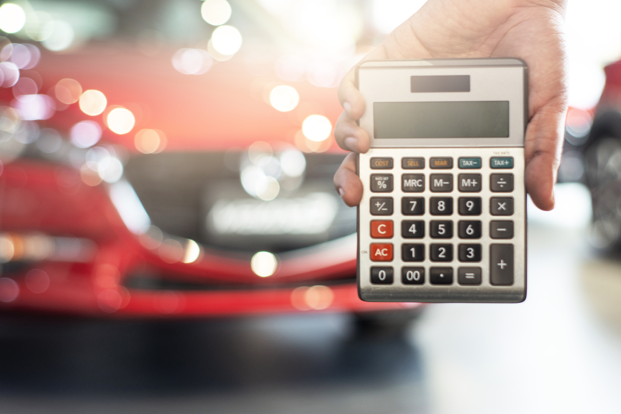 Asian man holding calculator for business finance on car showroom blurred bokeh background.for automotive automobile or transportation transport